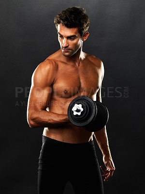 Buy stock photo Muscular man lifting dumbbell and looking away on black background