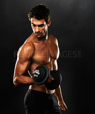 Buy stock photo Young muscular man lifting weights and looking away on black background