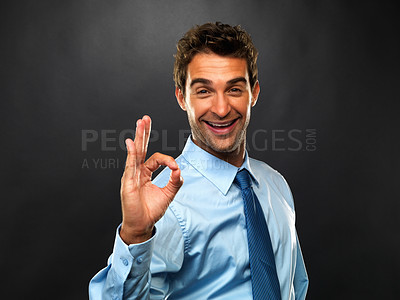 Buy stock photo Portrait of smiling business man giving you OK sign on black background