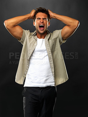 Buy stock photo Distressed young man screaming and pulling his hair on black background