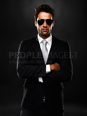 Buy stock photo Portrait of secret agent standing with hands folded on black background