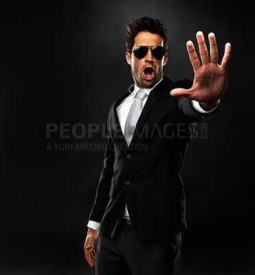 Buy stock photo Secret service agent with open palm gesturing to stop on black background