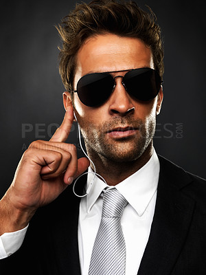 Buy stock photo Closeup of secret service employee talking on his earphones against black background