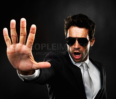 Buy stock photo Secret service agent standing on black background and holding out his hand gesturing to stop