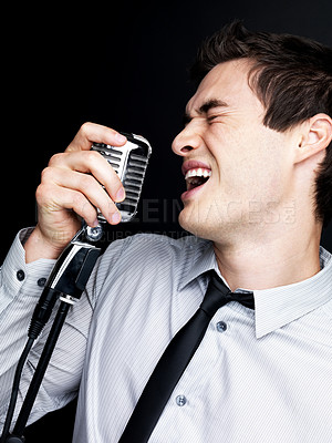 Buy stock photo Portrait of an excited young male jazz singer singing with old fashioned microphone against black background