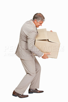 Buy stock photo Studio shot of a mature businessman carrying a heavy box against a white background