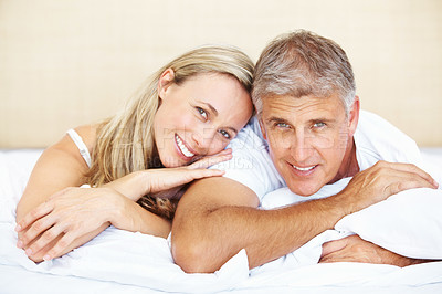 Buy stock photo Portrait of beautiful mature couple relaxing in their bed and looking at you at home
