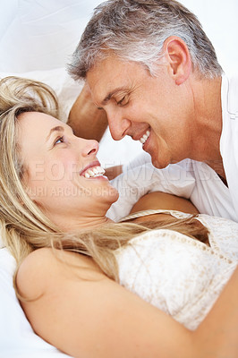 Buy stock photo Portrait of romantic couple lying together in bed at home