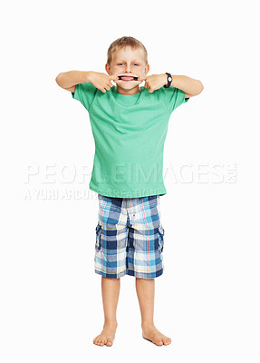 Buy stock photo Full length of mischievous young boy teasing over white background