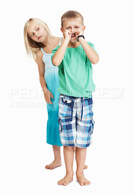 Buy stock photo Young boy teasing mischievously with girl standing back on white background
