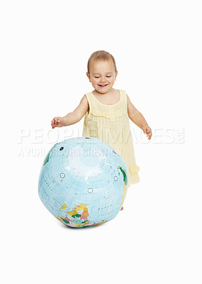Buy stock photo A cute toddler playing with a globe while isolated on white background