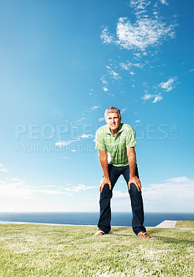 Buy stock photo Full length of mature man resting his hands on knees at park on a sunny day - copyspace