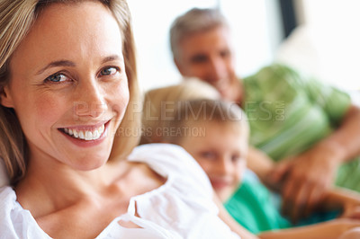 Buy stock photo Closeup of happy beautiful woman looking at you with her son and husband in the background