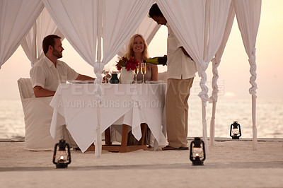 Buy stock photo Portrait of an attractive young couple having dinner on the beach under a luxurious pagoda