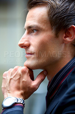 Buy stock photo Handsome young businessman looking to the side and showing his profile