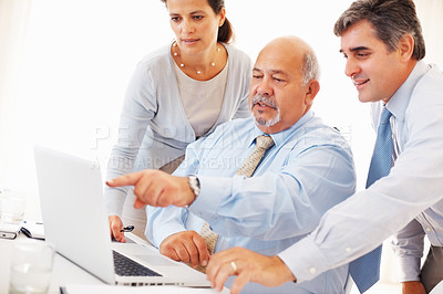 Buy stock photo Senior business man pointing at the laptop monitor with two executives near by