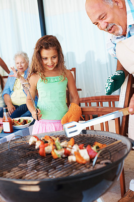 Buy stock photo Grandfather and grand daughter barbecuing food with grandmother in the background