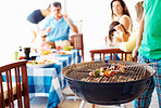 Focus on barbecue with family in background
