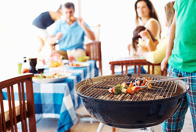 Buy stock photo Closeup of barbecue with family in background having meal together