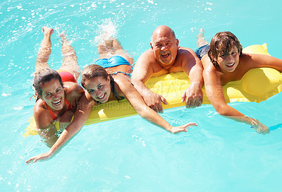 Buy stock photo Happy family of four floating on inflatable tube in water during vacation