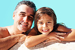 Father and daughter resting on the edge of swimming pool