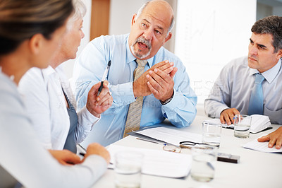 Buy stock photo Senior business man discussing with his colleagues during meeting