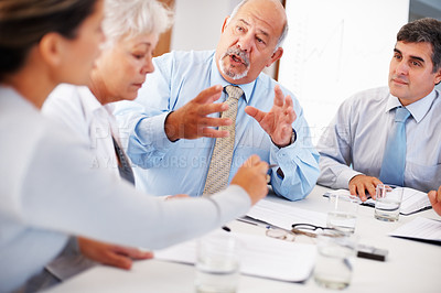 Buy stock photo Mature business man discussing with his colleagues during meeting