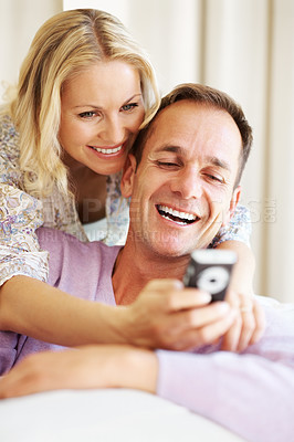 Happy couple reading a funny sms on cellphone