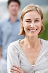 Mature woman smiling with a man in background