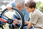 Aged man repairing a bicycle tyre with his grand son