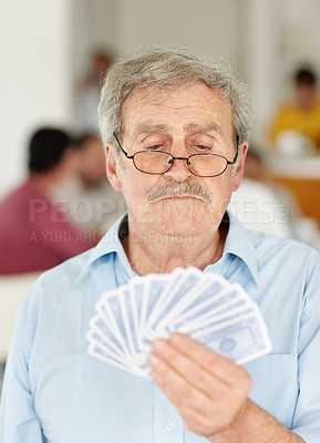 Old man playing a game of cards