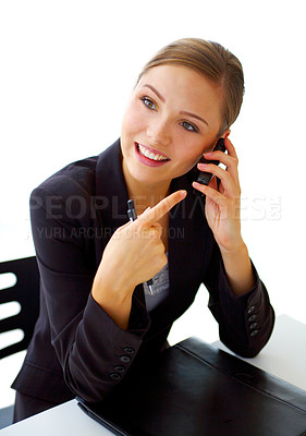 Buy stock photo Shot of a young businesswoman talking on her cellphone