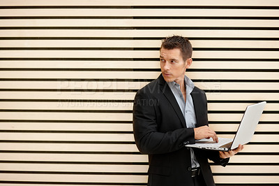 Buy stock photo Portrait of a young business man looking away anxiously while using a laptop - copypsace