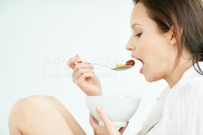 Young woman eating a bowl of fruits