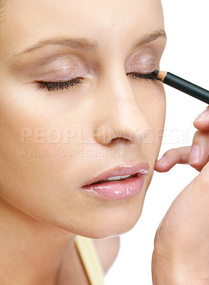Buy stock photo Closeup of a young woman applying eye liner on white background