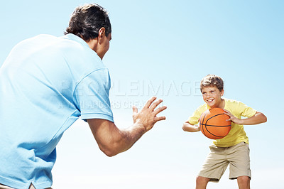 Buy stock photo Happy small kid playing basketball with his father against a blue sky outdoors