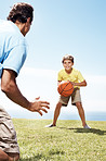 Little boy playing basketball with his father outdoors
