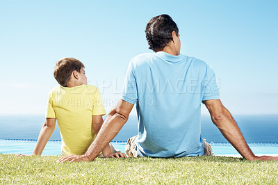 Buy stock photo Father and little son sitting on grass and looking at scene - Rear view
