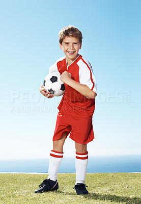 Buy stock photo Smiling liitle football player with a ball showing his muscles while standing outdoor