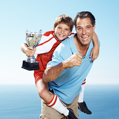 Buy stock photo Excited father piggybacking his champion  footballer son with a first prize tropy