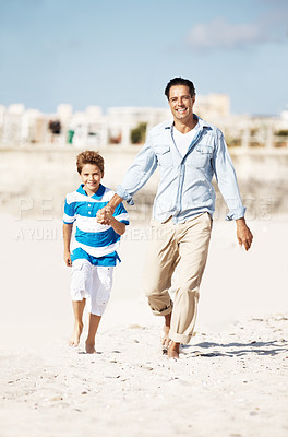Buy stock photo Portrait of father and son walking on the beach on a summer day