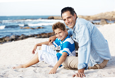 Buy stock photo Portrait of handsome young guy sitting with his son at a sandy beach on a summer day