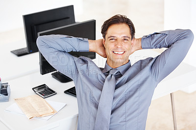 Buy stock photo Portrait of a businessman sitting relaxed in his chair with hands behind his head at work