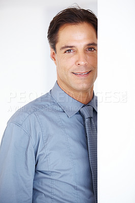 Buy stock photo Confident middle aged business man standing behind a wall and smiling