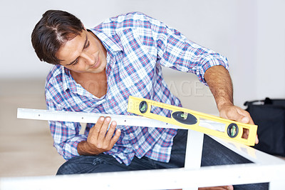 Buy stock photo Carpenter checking a level of a metal frame with bubble level tool in workshop
