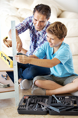 Buy stock photo Small boy learning from his father how to make a hole with a drill machine at home