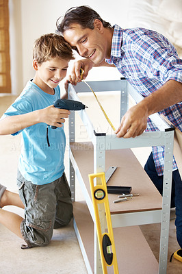 Buy stock photo Little kid learning from his father how to make a hole with a hand held drill at home