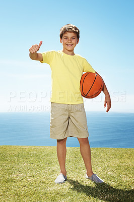 Buy stock photo Small boy holding a basketball in hand and giving a thumbs up sign while standing on grass outside