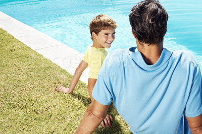 Buy stock photo Rear view of a happy man and his little son sitting relax by the swimming pool - Outdoor