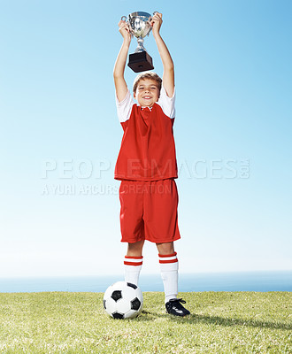 Buy stock photo Portrait of a happy little boy holding up a winners trophy with football at ground